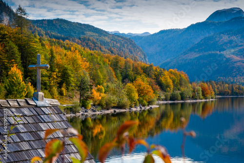 Foto Cross on the rooftop of a boathouse with autumn colors on the lake Grundlsee, Styria, Austria
