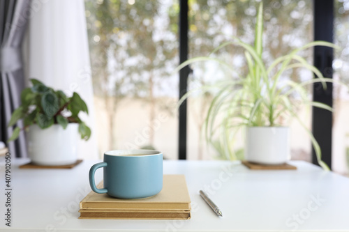 Blue modern matte coffee cup and pencil and brown notebook on white table with plants pot and keyboard © paladin1212