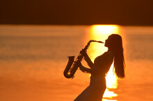 Saxophone, Music Instrument Played By Saxophonist Player Musician  In Lake On During Sunset