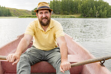 Adult Bearded Man Sitting In A Boat And Rowing Oars On A Summer Day