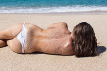 Shallow Focus Shot Of A Female Mo Lying On A Sandy Beach