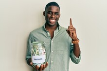 Young African American Man Holding Jar With Savings Smiling With An Idea Or Question Pointing Finger With Happy Face, Number One