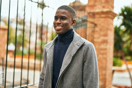Young african american man smiling happy standing at the city