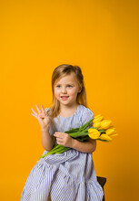 Happy Little Girl With A Bouquet Of Yellow Tulips And Shows Four Fingers On A Yellow Background With Space For Text