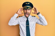Handsome Hispanic Man Wearing Airplane Pilot Uniform Crazy And Scared With Hands On Head, Afraid And Surprised Of Shock With Open Mouth