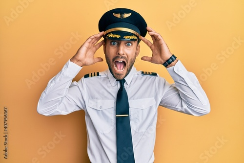 Handsome hispanic man wearing airplane pilot uniform crazy and scared with hands Fototapeta