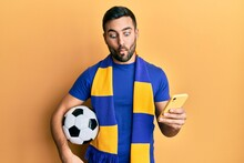 Young Hispanic Man Football Hooligan Holding Soccer Ball Using Smartphone Making Fish Face With Mouth And Squinting Eyes, Crazy And Comical.