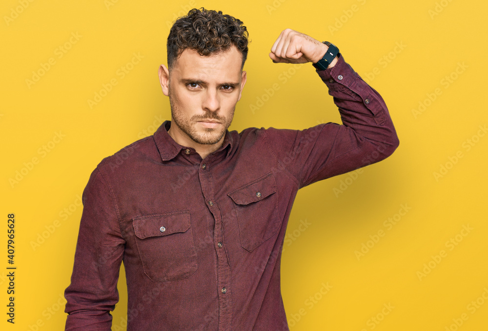 Fototapeta Young hispanic man wearing casual clothes strong person showing arm muscle, confident and proud of power