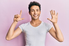 Young Handsome Man Wearing Casual White T Shirt Showing And Pointing Up With Fingers Number Seven While Smiling Confident And Happy.