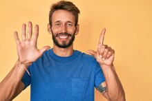Handsome Caucasian Man With Beard Wearing Casual Clothes Showing And Pointing Up With Fingers Number Seven While Smiling Confident And Happy.