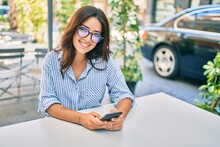 Young Hispanic Businesswoman Smiling Happy Using Smartphone At Coffee Shop Terrace.