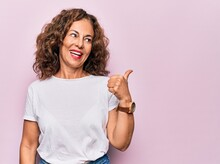Middle Age Beautiful Woman Wearing Casual T-shirt Standing Over Isolated Pink Background Pointing Thumb Up To The Side Smiling Happy With Open Mouth