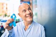 Middle age bald man smiling happy holding blue prostate cancer ribbon leaning on the wall at the city