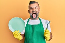 Middle Age Handsome Man Wearing Apron Holding Scourer Washing Dishes Sticking Tongue Out Happy With Funny Expression.