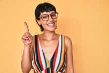 Beautiful Brunettte Woman Wearing Casual Clothes And Glasses Pointing Finger Up With Successful Idea. Exited And Happy. Number One.