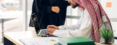 Photo Successful of two arab  business people working with laptop computer