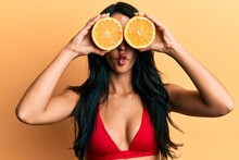 Beautiful Hispanic Woman Wearing Bikini Holding Orange On Eyes Making Fish Face With Mouth And Squinting Eyes, Crazy And Comical.