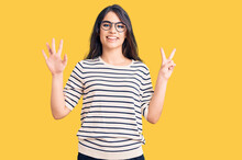 Brunette Teenager Girl Wearing Casual Clothes And Glasses Showing And Pointing Up With Fingers Number Seven While Smiling Confident And Happy.