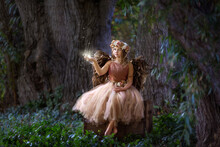 Young Girl As Fairy Or Angel Holding A Magical Crystal Ball In The Forest