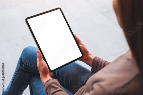 Obraz Mockup image of a woman holding digital tablet with blank white desktop screen - fototapety do salonu