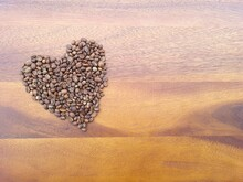 Love Or Valentine Concept. Closed Up Coffee Beans And Flowers In Heart Shape On Isolated Grey Wallpaper Background