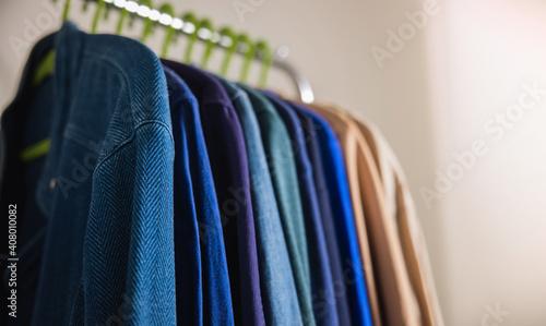 Obraz Wardrobe Rack. Men Clothes hanging on Bar by the White Wall. Fashion Lifestyle of a Stylish Man - fototapety do salonu