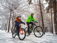 A Father And His Son Ride A Bikes In A Winter Park