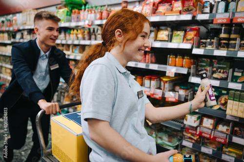 Fototapeta Supermarket employees having fun while working