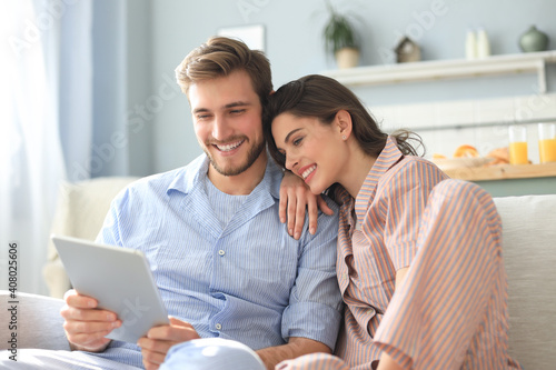 Fotografie, Obraz Young couple in pajamas watching media content online in a tablet sitting on a sofa in the living room