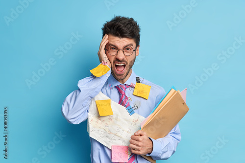 Irritated office worker exclaims with anger being overloaded with paper work holds folders with documentation wears round spectacles isolated over blue background. Angry employee stands indoor © Wayhome Studio