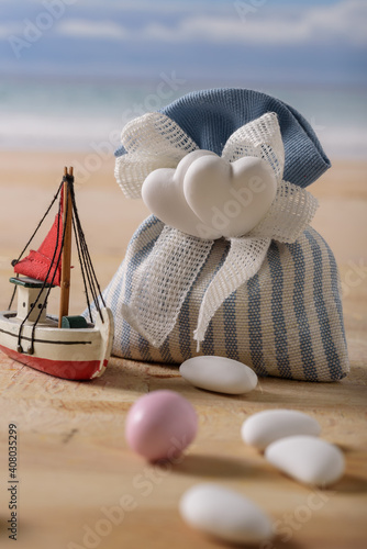 sweet food and a boat at  the seaside. still life with sweet almonds and a boat at the seaside. italian food to celebrate wedding and newborn. © marinzolich