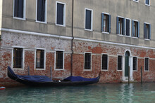 Gondola Against The Backdrop Of The Venice Building Near The Canal In Autumn During Quarantine Without Peopl
