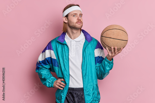 Obraz Serious man basketball player holds ball looks confidently at camera wears white headband sportsclothes enjoys playing favorite game isolated over pink background. Sport and recreation concept - fototapety do salonu
