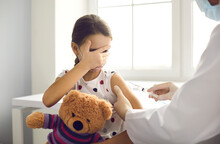 Little Kid Terrified By Injection At The Hospital. Girl Afraid Of Syringe Needle Covers Face While Getting Flu Vaccine At Pediatric Clinic. Doctor Giving A Shot To Scared Child Holding Teddy Bear Toy