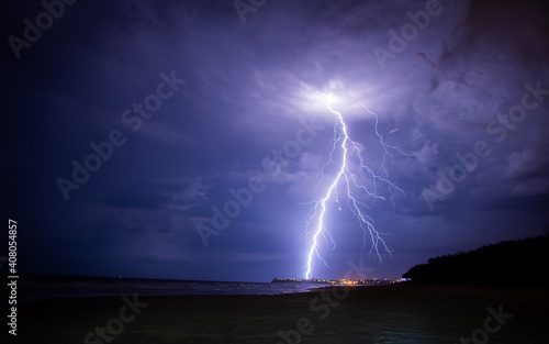 Obraz Lightening storm moving in over beach, with city. - fototapety do salonu
