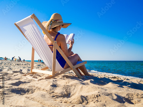 Woman relaxing on beach reading book sitting on sunbed Fototapet