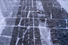 Car And Truck Wheel Marks On Snowy Road Texture In Winter