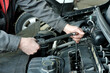 Maintenance and repair of cars in the service center. Close-up of the hands of a mechanic performing a torque wrench rotation of the bolts securing the engine cylinder head cover.