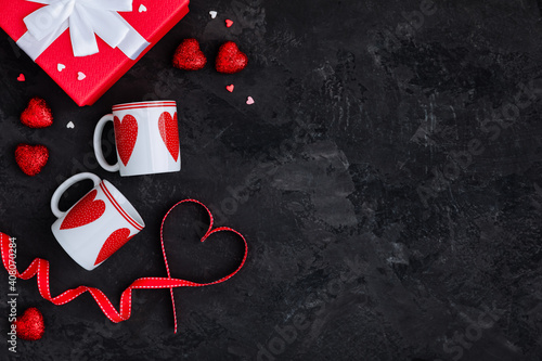 Valentines Day background with two cups, present box and red ribbon with heart and present box © nblxer