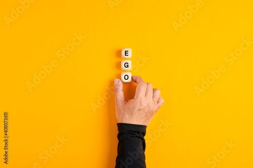 Платно Male hand placing the wooden blocks with the word Ego on yellow background