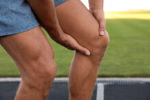 Man In Sportswear Having Knee Problems At Stadium, Closeup