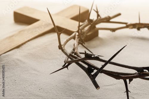 Photo Crown of thorns and wooden cross on sand, closeup