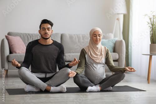 Obraz Prenatal Yoga Concept. Pregnant religious muslim couple meditating together at home - fototapety do salonu