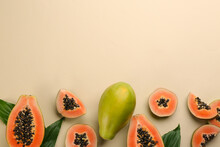 Fresh Ripe Papaya Fruits With Green Leaves On Beige Background, Flat Lay. Space For Text