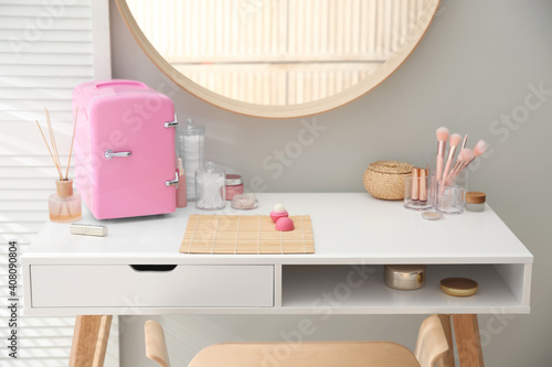 Obraz Cosmetics refrigerator and skin care products on white vanity table indoors - fototapety do salonu