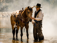 A Young Cowboy Rested With A Horse In The Stream After He Finished Showering The Horse