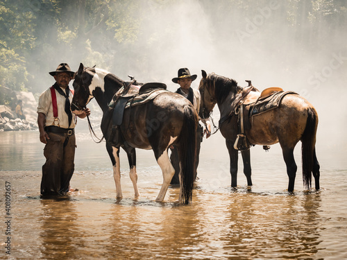 Fotografie, Obraz Old cowboy and young cavalry  rest with their horses in the stream after they fi