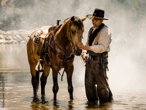 Photo A young cowboy rested with a horse in the stream after he finished showering the