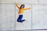 Fototapeta Miasto - Happy woman jumping against concrete wall in the city
