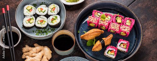 japanese sushi food. Maki ands rolls with tuna, salmon, shrimp, crab and avocado. Top view of assorted sushi. Rainbow sushi roll, uramaki, hosomaki and nigiri. © karepa